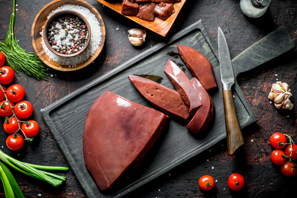 Sliced raw liver with tomatoes, herbs and spices. On dark rustic background