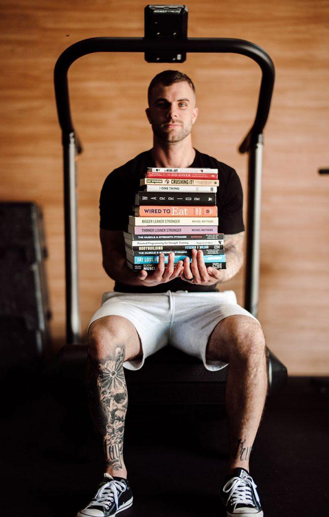 Cody McBroom holding a pile of books
