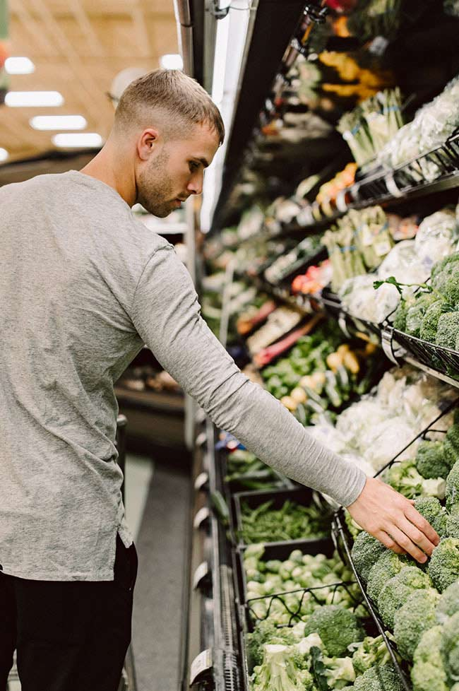A man selecting vegetables at the supermarket